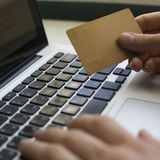 Credit card in hand and entering security code using laptop keyboard. Royalty Free Stock Image