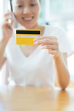 credit card in hand of female speaking mobile Royalty Free Stock Photography