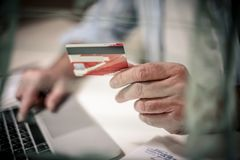 Credit card in hand. Senior business man checking his finance on credit card. Close up. Focus is on hand Royalty Free Stock Photography