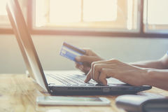 Credit card. Hands holding credit card and using laptop. Online shopping royalty free stock photos