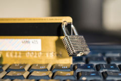 Credit card with hanging padlock on keyboard Royalty Free Stock Images