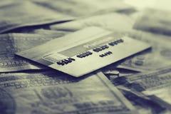 Credit card on hundres dollar bills closeup. Vintage style Royalty Free Stock Photo