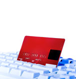 Credit card on keyboard close up. Online shopping, red credit card on white keyboard close up Stock Photography