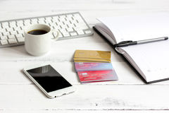 Credit card, keyboard, smartphone and coffee cup on wooden background Royalty Free Stock Photos