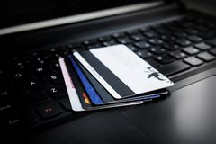 Credit card on a laptop. Credit cards on a laptop. Several credit and discount cards are on the keyboard of a black laptop. Online payment. Cashless settlement Stock Photo
