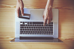 Credit card and laptop. Hands holding credit card and using laptop. View from above Stock Photos