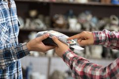 Credit card machine holding by man hands. A gray card entering under the machine, close up Royalty Free Stock Photography