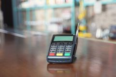 Credit card machine for non cash payment on wooden counter in cafe. Space for text stock photography