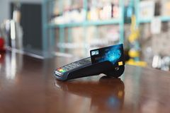 Credit card machine for non cash payment on wooden counter in cafe. Space for text stock images