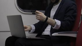 On credit card man on laptop makes purchases online on the road. stock video