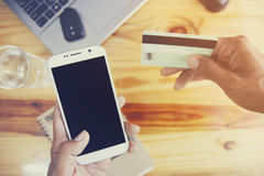 Credit card. Man's hands holding a credit card and using smart phone for online shopping Royalty Free Stock Photography