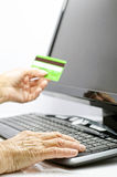 Credit card in mature hands. Old woman with credit card and computer Stock Images
