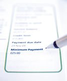 Credit card: minimum payment. An image of a credit card statement with selective focus showing a pen pointing to the minimum payment amount Stock Images