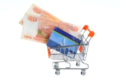 Credit card and money within shopping cart isolated on white Royalty Free Stock Images