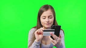 Credit Card for Online Transaction. Beautiful woman online banking using smartphone shopping online with credit card on green screen background stock footage