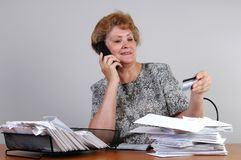 Credit Card Order. A woman with a pile of bills makes a credit card order by phone Stock Photography