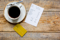 Credit card for paying, coffee and check on cafe wooden desk background top view mock up Royalty Free Stock Image