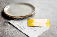 Credit card for paying, plate and check on cafe stone desk background Stock Images
