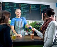 Credit card payment. Bertender receiving credit card of customer for payment in cafe Stock Photography