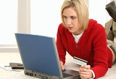 Credit Card Payment. Casual young woman at home making online credit card payments Stock Photography