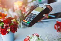 Credit card payment. Florist shop owner holding credit card terminal Stock Photo