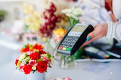 Credit card payment. Florist shop owner holding credit card terminal Royalty Free Stock Photo