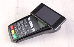 Payment terminal and mobile phone with NFC technology, cashless paying for shopping or products. Credit card reader, payment terminal and mobile phone with NFC Stock Image