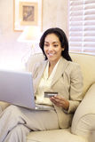 Credit card shopping. Young attractive Hispanic woman indoors sitting with a laptop and credit card making an on-line purchase Royalty Free Stock Image