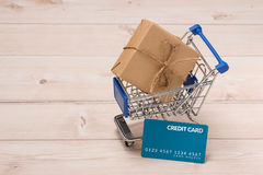 Credit card and shopping cart with gift box wrapped with paper k. Raft on table Stock Photo