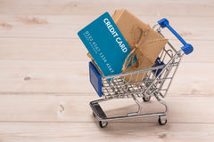 Credit card and shopping cart with gift box wrapped with paper k. Raft on table Royalty Free Stock Photo