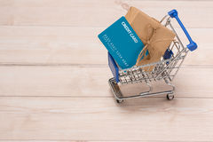 Credit card and shopping cart with gift box wrapped with paper k. Raft on table Royalty Free Stock Image