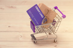 Credit card and shopping cart with gift box wrapped with paper k. Raft on table Royalty Free Stock Images