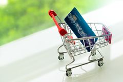 Credit card on shopping cart trolley on white table with green backgrounds Royalty Free Stock Photo