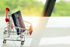 Credit card on shopping cart trolley on white table with green backgrounds Stock Photos
