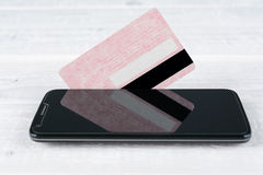 Credit card and smartphone lying on a wooden table Royalty Free Stock Photo