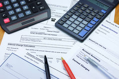 Credit Card Statements. A desk covered with credit card statements, two calculators, a few pens and a blank check Royalty Free Stock Images