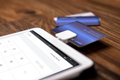 Credit Card Swipe Reader. Credit card payment on a swipe or chip reader app on a tablet used by small or online businesses.  The electronic device is used as a Royalty Free Stock Image