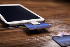 Credit Card Swipe Reader. Credit card payment on a swipe or chip reader app on a tablet used by small or online businesses.  The electronic device is used as a Stock Photos