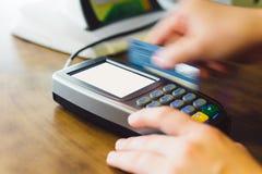 Credit card swiping on tetminal. Close up of hand swipe credit card on card-reader machine Stock Photo
