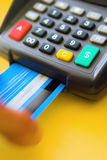 Credit Card Terminal. A credit card terminal on a golden yellow background, with credit card insertion (motion blur). Dollar sign on the green button. shallow Royalty Free Stock Photos