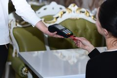 Credit card terminal for cashless payments. Cashier holds card reader. Credit card terminal for cashless payments. Cashiers hand holds credit card reader on Royalty Free Stock Photography