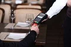 Credit card terminal for cashless payments. Credit card payment. And electronic bank concept. Customer puts credit card into machine. Cashiers hand holds credit Stock Photography