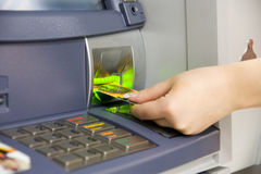 Credit cards. Hand holding credit cards through automaton Stock Photography