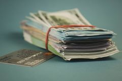 Credit cards and a bundle of money on a plain blue background royalty free stock photo