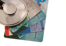 Credit crisis. Stethoscope on a stack of credit cards over a white background royalty free stock photos