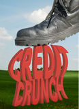 Credit crunch. The words credit crunch being squashed by a workmans boot set against an idylic background stock photography