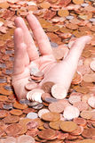 Credit crunch. A hand sinking in a sea of coins reflecting credit and debt Royalty Free Stock Photography