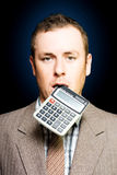 Credit crunch or financial struggle. Dazed tired accountant dangles a calculator out of his mouth after crunching endless numbers to find a solution to debt and Royalty Free Stock Photos