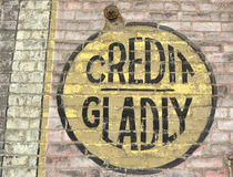 Credit Gladly. An old and fading sign, offering credit, painted on a brick wall Royalty Free Stock Photo