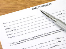Credit Inquiry Form On Desk. Credit inquiry form with a brushed silver and chrome pen on desk Royalty Free Stock Photo